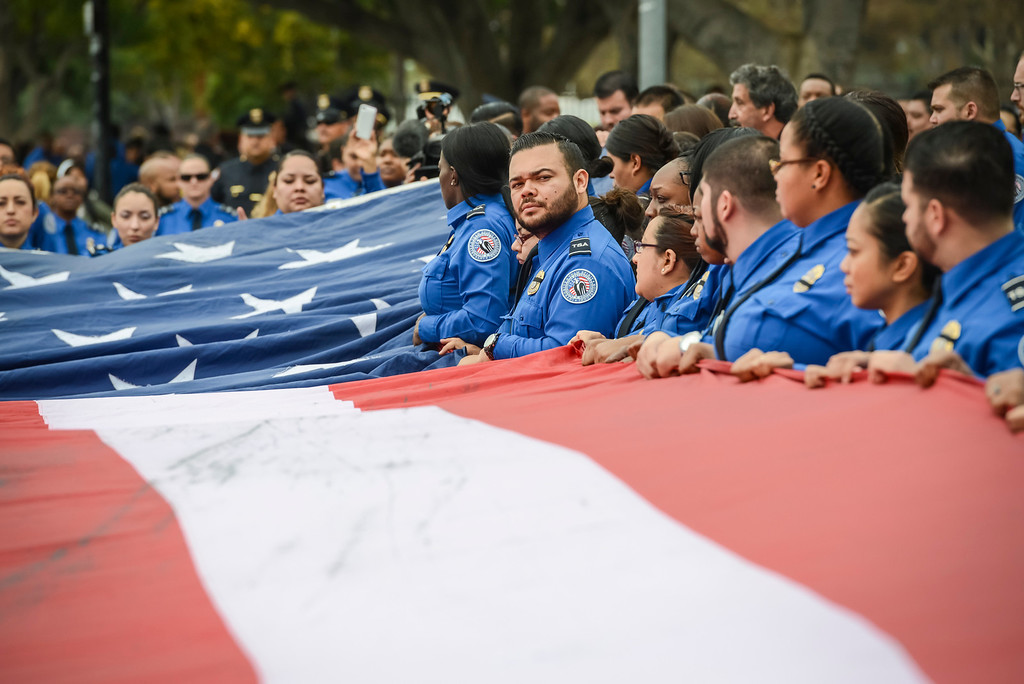 . TSA officers fold a giant US flag at the memorial for slain TSA officer Gerardo Hernandez at the Los Angeles Sports Arena Tuesday, November 12, 2013.  A public memorial was held for Officer Hernandez who was killed at LAX when a gunman entered terminal 3 and opened fire with a semi-automatic rifle.  ( Photo by David Crane/Los Angeles Daily News )