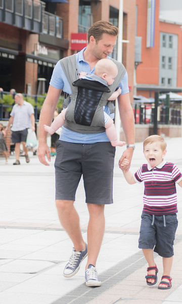 Izmi_Baby_Carrier_Breeze_Mid_Grey_Lifestyle_Front_Carry_Dad_Shopping_Holding_Sons_hand.jpg