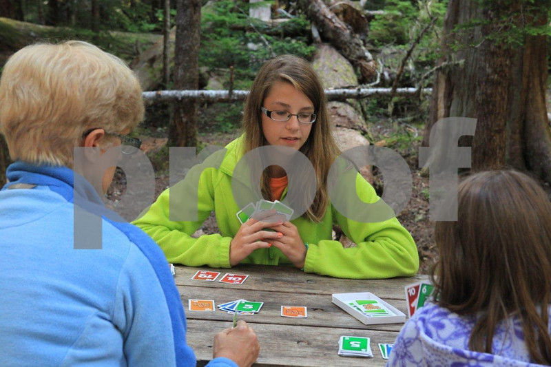 Playing a game of cards while dinner cooks at the camp site.