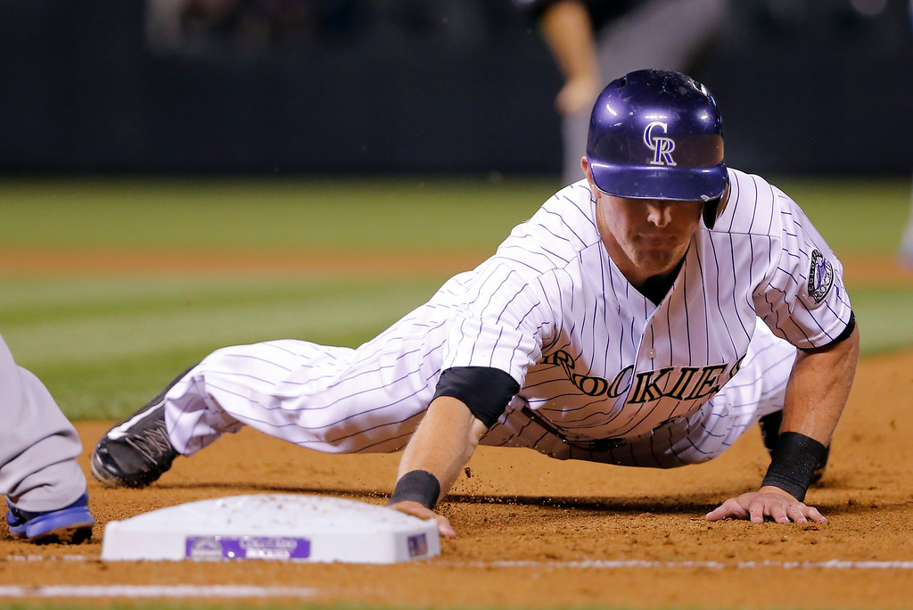 . Colorado Rockies\' Drew Stubbs dives back to first to beat the throw during the fourth inning of a baseball game against the Los Angeles Dodgers Tuesday, Sept. 16, 2014, in Denver. (AP Photo/Jack Dempsey)