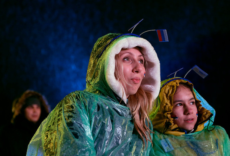 . Salina Anatolevna, left, and Valieva Dmitrievna, watch a bobsled competition on a large video screen at the Sochi 2014 Winter Olympics, Tuesday, Feb. 18, 2014, in Krasnaya Polyana, Russia. (AP Photo/Charlie Riedel)