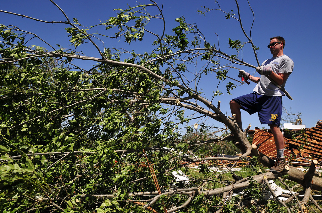 . Josh Hill, a volunteer with Grace Chapel in Englewood, Colo., helps to clear downed branches from Angela and Wade Burleson\'s yard in El Reno Okla. on Saturday June 1, 2013 after their home was destroyed by one of the tornados that swept through Central Okla. on Friday. (AP Photo/Nick Oxford)