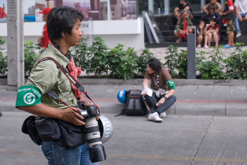 A photographer holds his camera while covering the Red Shirt Protest in Thailand