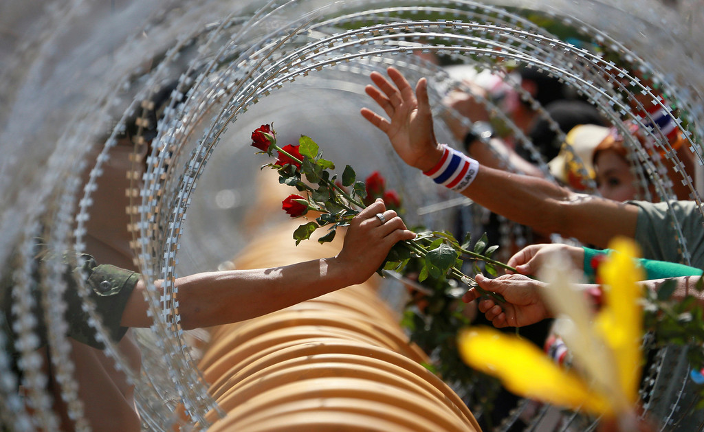 . An anti-government protester gives a rose to a Thai soldier at the Defense Ministry during a rally in Bangkok Thursday, Nov. 28, 2013. Thailand\'s embattled prime minister begged protesters who have staged the most sustained street rallies in Bangkok in years to call off their demonstrations and negotiate an end to the nation\'s latest crisis. (AP Photo/Wason Wanichakorn)