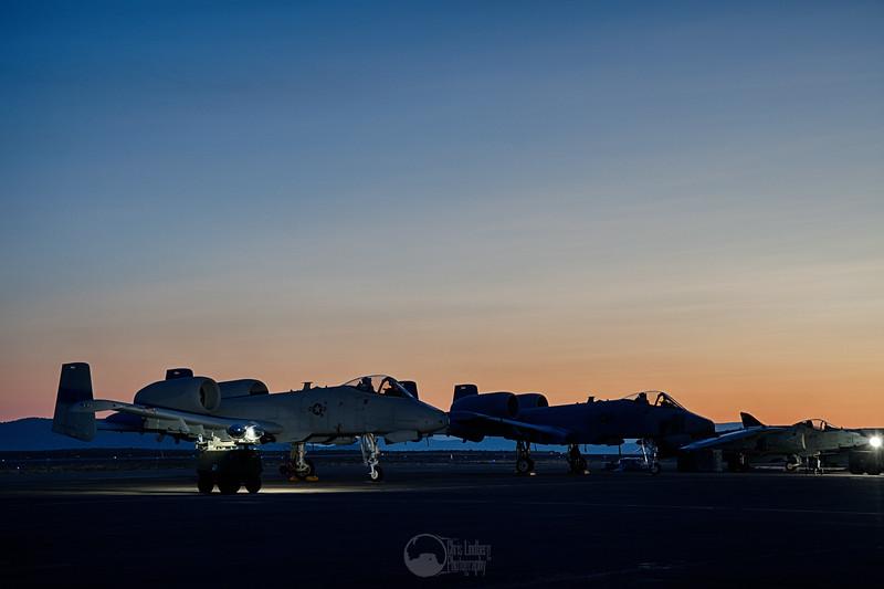 Twin A-10C Thunderbolt IIs and an AV-8B Harrier II at Dawn
