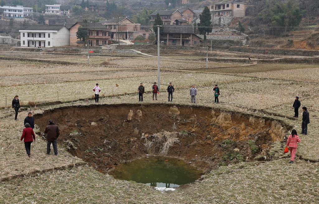 . People stand by a recent caved-in area on a paddy field in Fukou county, Hunan province, January 12, 2013. More than 20 pits formed from the sunken ground surface in Fukou county during the past four months. According to the local media, the government\'s initial investigation showed years of mining destroyed the local underground water systems and led to the numerous cave-ins. Picture taken January 12, 2013. REUTERS/China Daily