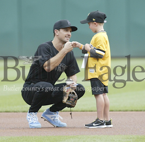 Prior to the Pirates / Reds game. Zachary Emsurak, 7, of Saxonburg, is greeted at second base by Pirate, Adam Frazier. Zack fist bumps Adam after receiving a signed baseball. Sunday August 25, 2019 photo by Ed Nebel