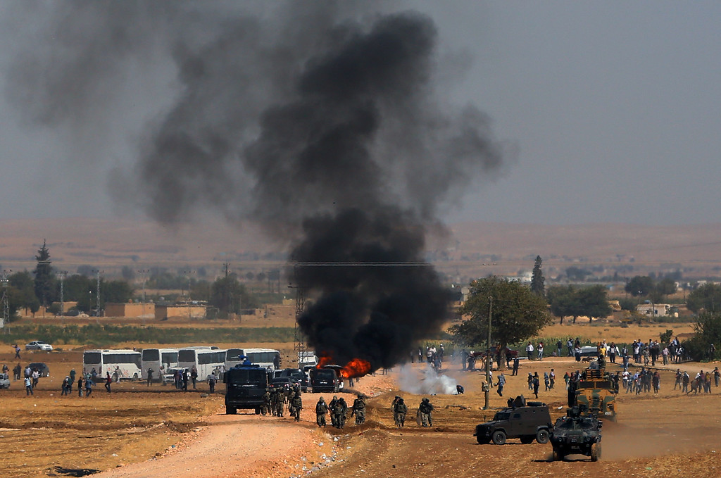 . A car hit by a teargas canister burns as riot police use teargas to disperse Kurdish demonsrators as thousands of Syrian refugees continue to arrive at the border in Suruc, Turkey, Monday, Sept. 22, 2014.  (AP Photo/Burhan Ozbilici)