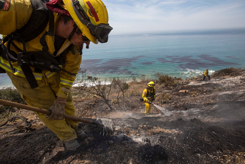 . Firefighters work on the burned area along the PCH, in Point Mugu, Calif., Friday, May 3, 2013.  A huge wildfire carved a path to the sea and burned on the beach Friday, but firefighters got a break as gusty winds turned into breezes. Temperatures remained high, but humidity levels were expected to soar as cool air moved in from the ocean and the Santa Ana winds retreated. (AP Photo/Ringo H.W. Chiu)
