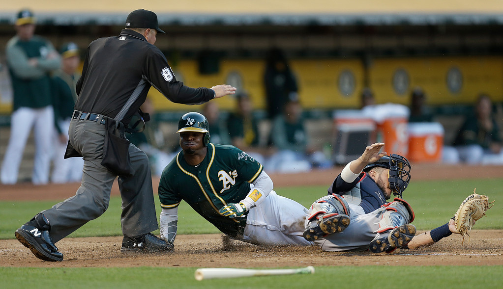 . Oakland Athletics\' Rajai Davis, middle, scores past Cleveland Indians catcher Yan Gomes during the third inning of a baseball game Friday, July 14, 2017, in Oakland, Calif. Home plate umpire Cory Blaser, left, makes the call. (AP Photo/Ben Margot)