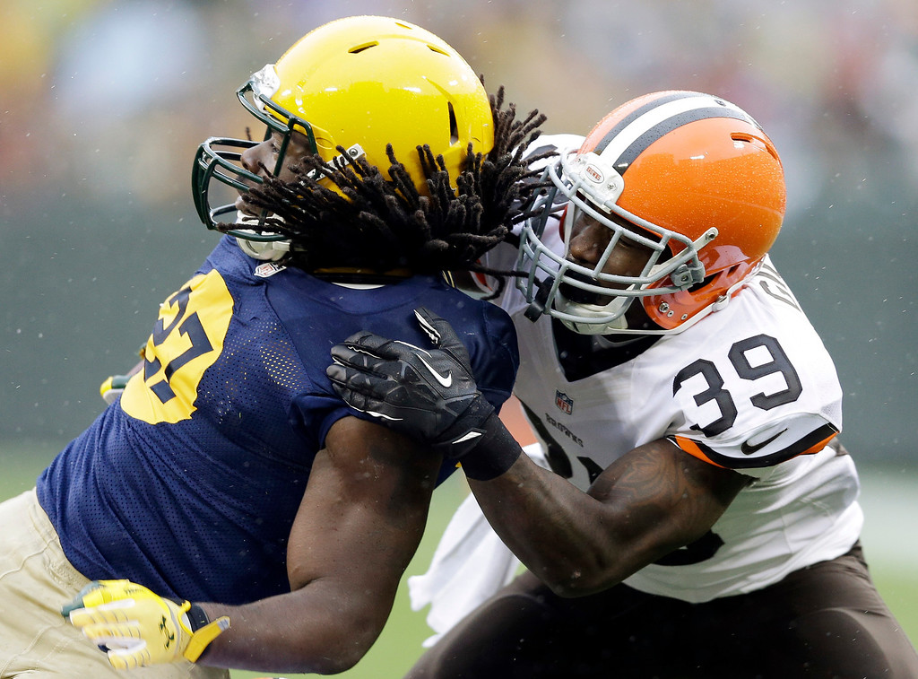 . Green Bay Packers running back Eddie Lacy (27) is tackled by Cleveland Browns\' Tashaun Gipson during the first half of an NFL football game Sunday, Oct. 20, 2013, in Green Bay, Wis. (AP Photo/Tom Lynn)