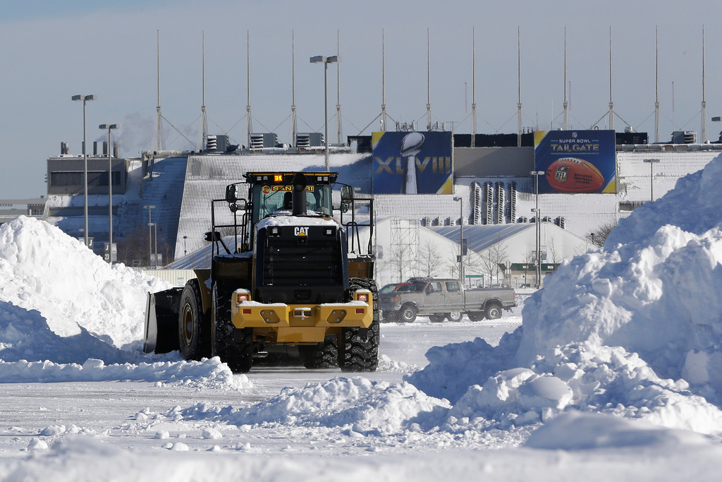 . A tractor plows snow off the parking lot of MetLife Stadium as crews removed snow following a snow storm, Wednesday, Jan. 22, 2014, in East Rutherford, N.J.  (AP Photo/Julio Cortez)
