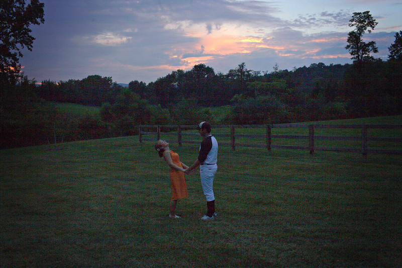 """Even with the graininess of this photo there is so much I love about it. I was actually just playing with the camera to try a silouette and you guys were messing around. I love that he made you laugh. I love that you are in a dress and he is in a baseball uniform. Looks like a proposal. reminds me of the movie """"Never Been Kissed"""" as they meet on the ballfield. decided to keep it...ordinarily would have thrown it out."""