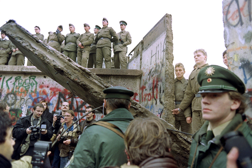 """. Two West German policemen prevent people from approaching as East German Vopos stand on and near a fallen portion of the Berlin Wall 11 November 1989. Two days before, Gunter Schabowski, the East Berlin Communist party boss, declared that starting from midnight, East Germans would be free to leave the country, without permission, at any point along the border, including the crossing-points through the Wall in Berlin. The Berlin concrete wall was built by the East German government in August 1961 to seal off East Berlin from the part of the city occupied by the three main Western powers to prevent mass illegal immigration to the West. According to the \""""August 13 Association\"""" which specializes in the history of the Berlin Wall, at least 938 people - 255 in Berlin alone - died, shot by East German border guards, attempting to flee to West Berlin or West Germany. (Photo credit GERARD MALIE/AFP/Getty Images)"""