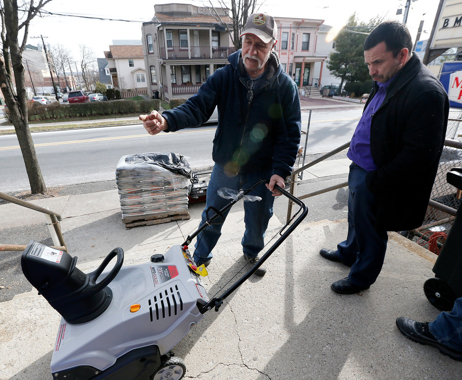 . Dominick Pisciotta, left, teaches customer Mario Argueta how to use a snow blower  while conducting a sale at Meadowlands Hardware ahead of the weekend\'s snowstorm, Friday, Jan. 22, 2016, in Rutherford, N.J. Towns across the state are hunkering down in preparation for a major snowstorm expected to begin later in the day. (AP Photo/Julio Cortez)