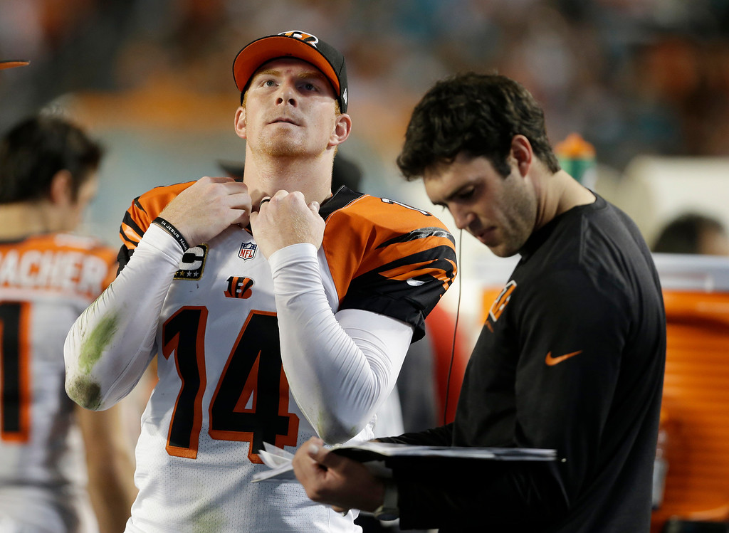 . Cincinnati Bengals quarterback Andy Dalton (14) looks up before looking at play copies on the sideline during the first half of an NFL football game against the Miami Dolphins, Thursday, Oct. 31, 2013, in Miami Gardens, Fla. (AP Photo/Lynne Sladky)
