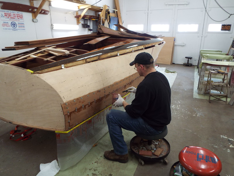 Rear starboard view of the first two planks installed and the excess epoxy being cleaned.