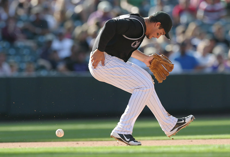 . Colorado Rockies third baseman Nolan Arenado looks for ball after knocking down ground ball hit by Miami Marlins pinch-hitter Reed Johnson before putting out Johnson at first base in the eighth inning of the Rockies\' 7-4 victory in a baseball game in Denver on Sunday, Aug. 24, 2014. (AP Photo/David Zalubowski)
