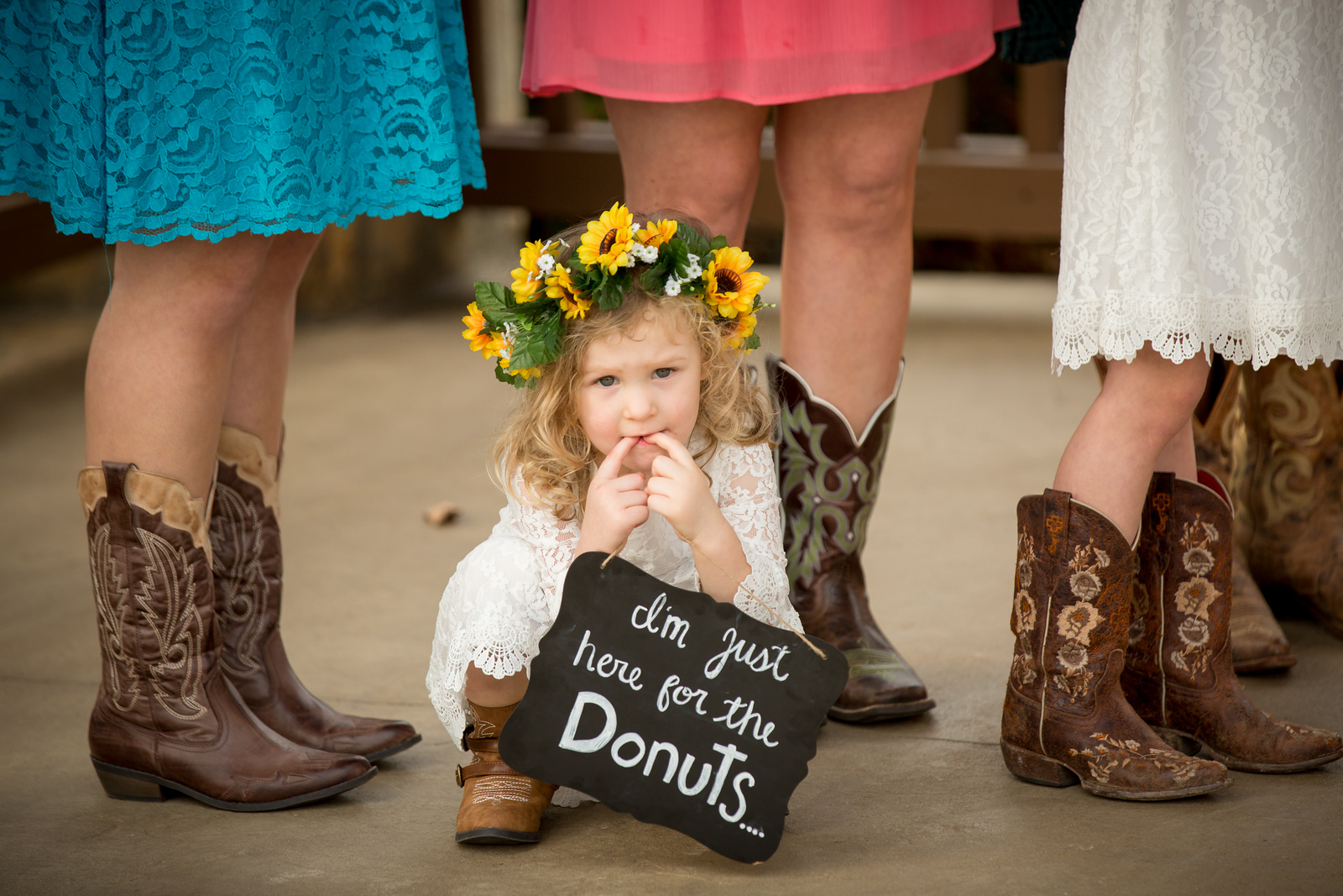 a young flower girl wearing cowboy boots holding a sign reading I'm just here for the donuts.