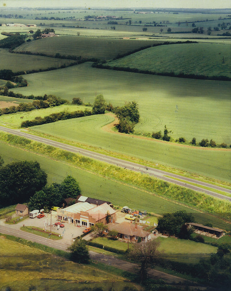 Photo of the Spaldwick Service Station. Note that the A604 had been constructed and it was single lane in each direction. You can see kennels and and old cottage on the right of the garage. You can also see a horse in the field to the left!