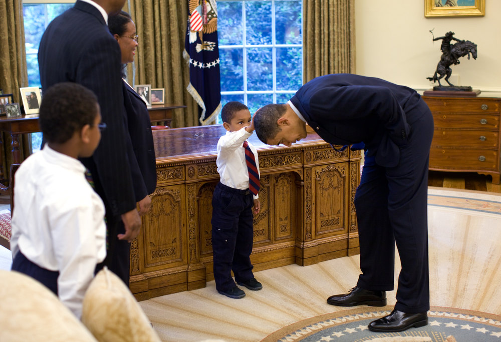 "Description of . May 8, 2009 ""A temporary White House staffer, Carlton Philadelphia, brought his family to the Oval Office for a farewell photo with President Obama. Carlton's son softly told the President he had just gotten a haircut like President Obama, and asked if he could feel the President's head to see if it felt the same as his.""  (Official White House photo by Pete Souza)"