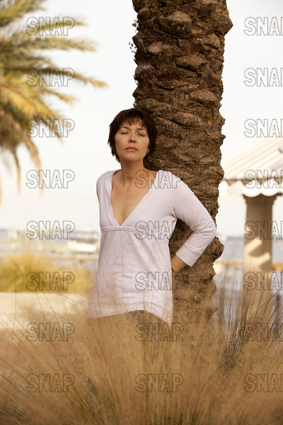 A beautiful young woman posing while leaning against a palm tree with a boathouse and river in the background.