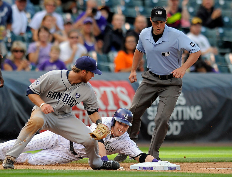 . Colorado Rockies\' Corey Dickerson, center, is tagged out at third base by San Diego Padres third baseman Cory Spangenberg, left, after he overshot the base in the seventh inning of a baseball game Sunday, Sept. 7, 2014, in Denver. The Rockies won 6-0. Third base umpire Quinn Wolcott, right, watches the play. (AP Photo/Chris Schneider)