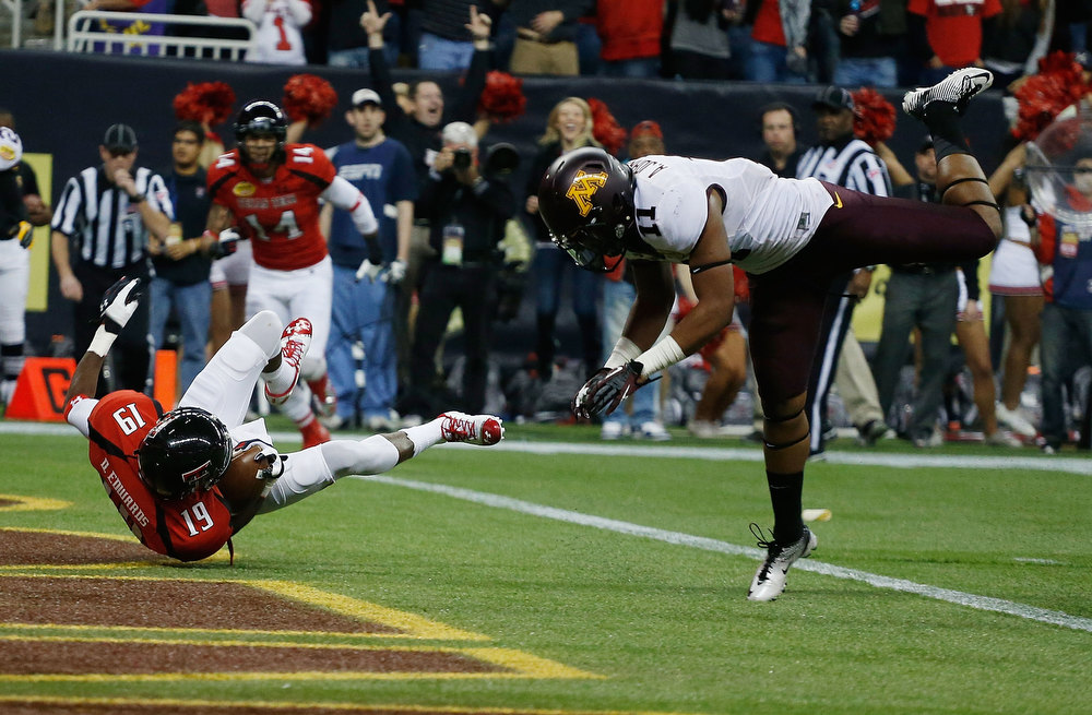 Description of . Derreck Edwards #19 of Texas Tech falls into the end zone for a first quarter touchdown against Antionio Johnson #10 of Minnesota during the Meineke Car Care of Texas Bowl at Reliant Stadium on December 28, 2012 in Houston, Texas.  (Photo by Scott Halleran/Getty Images)