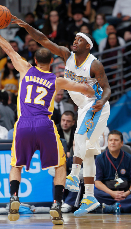 . Denver Nuggets guard Ty Lawson, right, passes ball over Los Angeles Lakers guard Kendall Marshall in the first quarter of an NBA basketball game in Denver on Friday, March 7, 2014. (AP Photo/David Zalubowski)