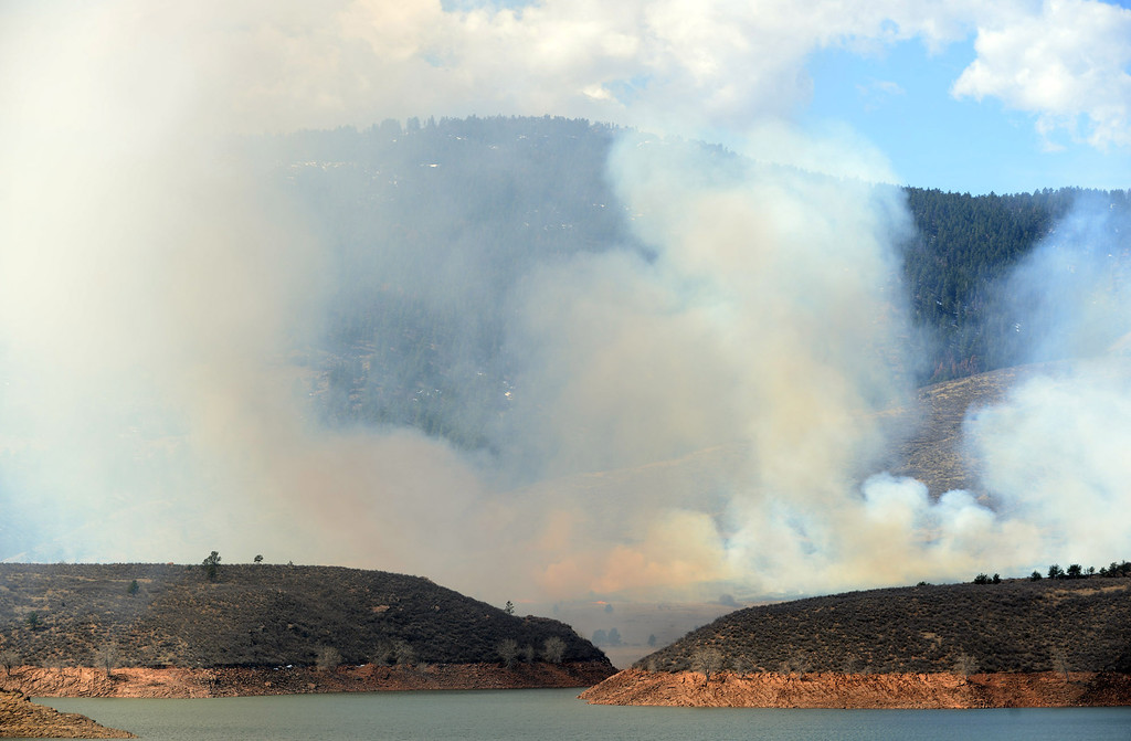 . Smoke rises as a wildfire burns out of control at Horsetooth Reservoir west of Fort Collins, Colo., on Friday, March 15, 2013. The 40-acre wildfire burning in gusty winds and warm weather was threatening homes west of Fort Collins on Friday and prompted about 50 people to leave the area. (AP Photo/The Coloradoan, V. Richard Haro)