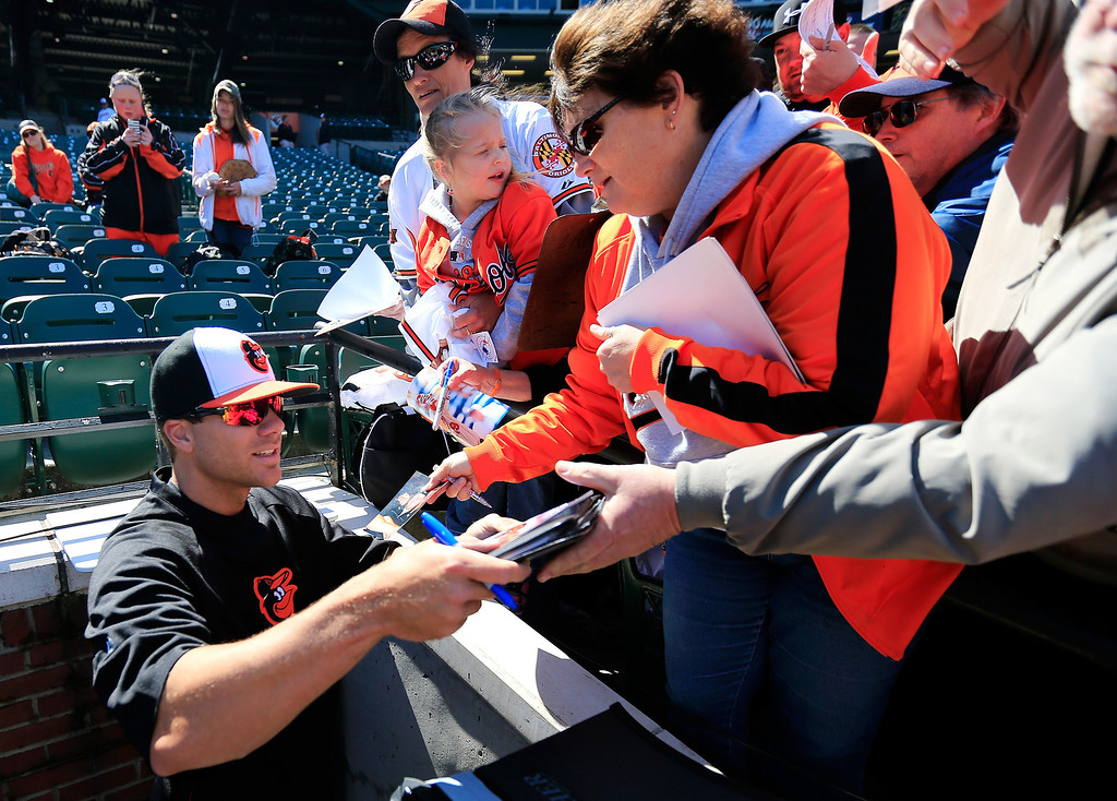 . Chris Davis #19 of the Baltimore Orioles signs autographs before the start of the Orioles and Boston Red Sox Opening Day game at Oriole Park at Camden Yards on March 31, 2014 in Baltimore, Maryland.  (Photo by Rob Carr/Getty Images)