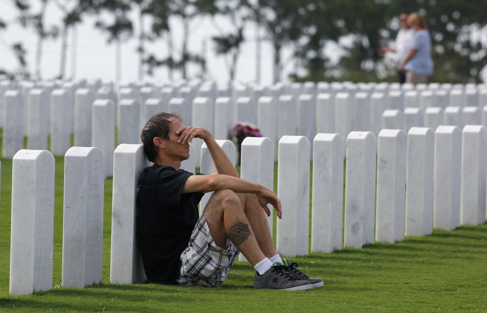. Jeff Lee of Lantana, Florida, leans against the gravestone of his father, Frank Lee, during a Memorial Day ceremony at the South Florida National Cemetery in Lake Worth, Florida May 27, 2013. REUTERS/Joe Skipper