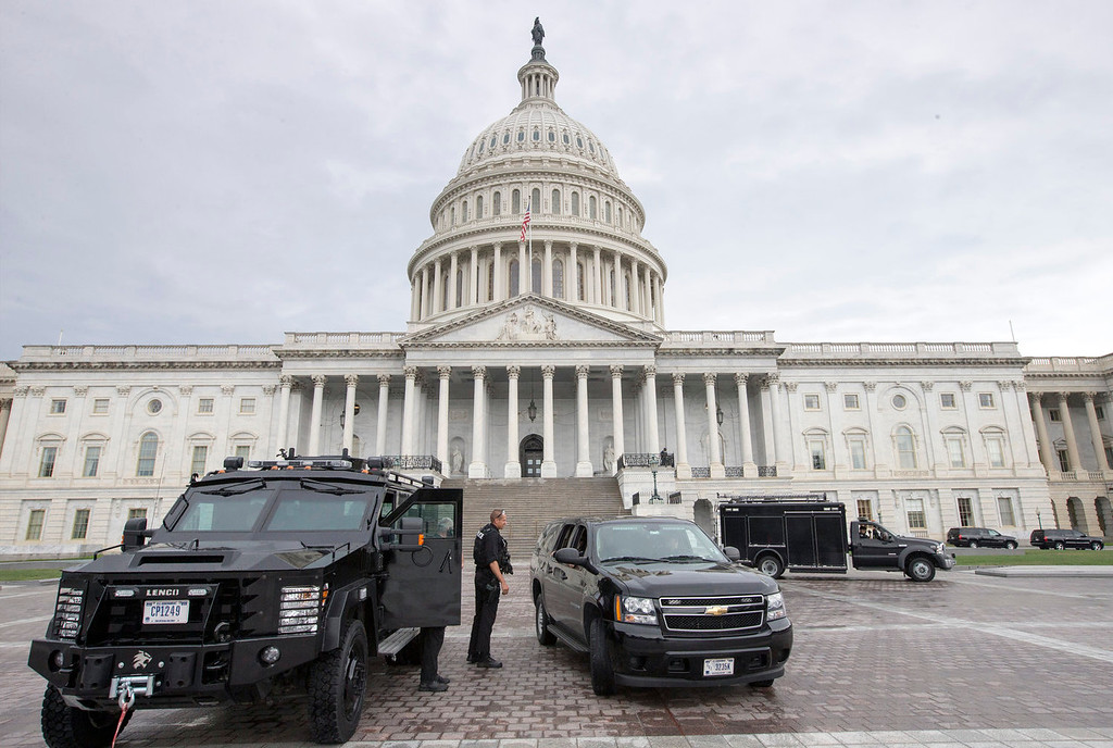 . U.S. Capitol Police personnel keep watch on the East Plaza of the Capitol as the investigation continues to the shooting at the nearby Washington Navy Yard  Monday, Sept. 16, 2013, in Washington. At least one gunman opened fire inside a building at the Washington Navy Yard on Monday morning, and officials said six people were killed and as many as 10 were wounded, including a law enforcement officer. (AP Photo/J. Scott Applewhite)