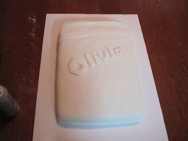 The frosted cake has been covered in white fondant, with additional layers of fondant used to represent torn pages.  Olivia's name has been stenciled in fondant letters, to be sprayed with the edible black color mist seen on the left.