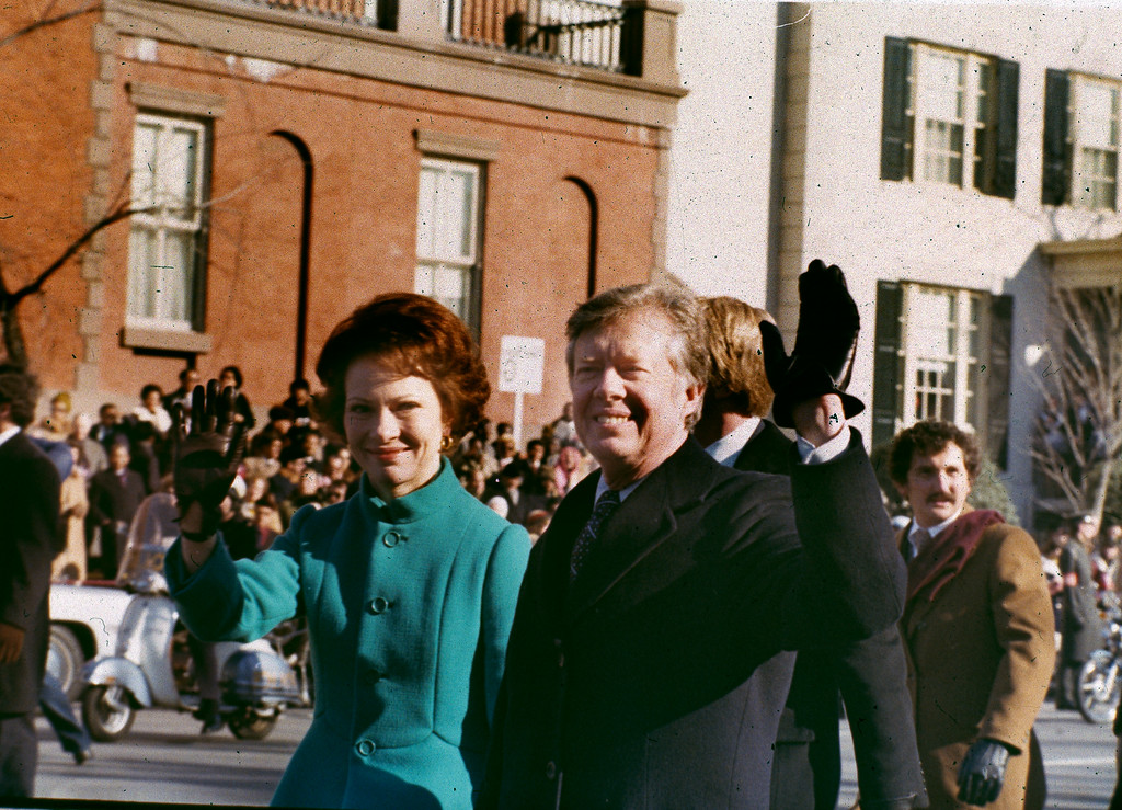 . U.S. President Jimmy Carter, right, and his wife, first lady Rosalynn Carter, wave to the crowd as they walk down Washington\'s Pennsylvania Avenue, Jan. 20, 1977.  Carter was sworn in as the 39th president of the United States during the inauguration ceremonies.  (AP Photo)