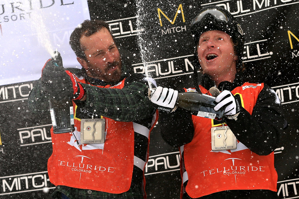 . (L-R)  Seth Wescott and Nate Holland of the USA celebrate with champagne on the podium after winning the USANA Snowboardcross World Cup Team Event on December 15, 2012 in Telluride, Colorado.  (Photo by Doug Pensinger/Getty Images)