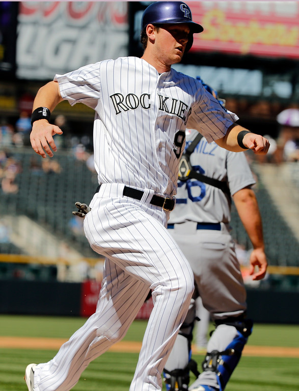 . Colorado Rockies\' DJ LeMahieu scores against the Los Angeles Dodgers during the first inning of a baseball game Wednesday, Sept. 17, 2014, in Denver. (AP Photo/Jack Dempsey)