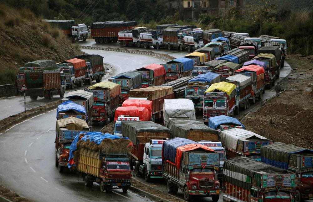 . Stranded trucks wait for the Jammu-Srinagar highway to reopen on the outskirts of Jammu, India, Tuesday, Feb. 5, 2013. Following fresh snowfall and landslides in some areas, the Srinagar-Jammu highway remained closed for the second consecutive day Tuesday. (AP Photo/Channi Anand)