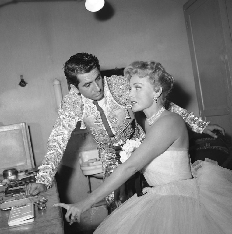 ". French star Daniel Gelin checks American star Zsa Zsa Gabor\'s make-up before filming of a sequence for a movie, ""Sang et Lumiere\"" (Blood and Lights) on Aug. 30, 1953 in Paris.  Gelin is dressed for his role as a matador.  (AP Photo)"
