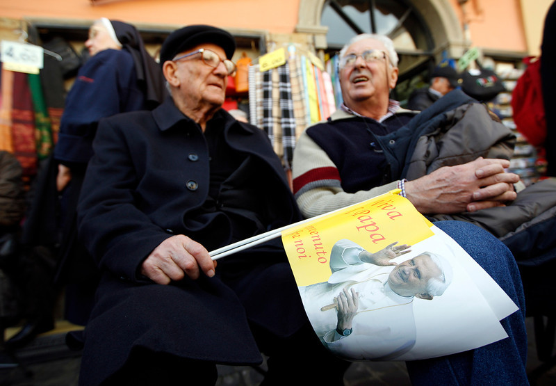 . Two men sit in front of the pope\'s summer residence in Castel Gandolfo, the scenic town where Pope Benedict XVI will spend his first post-Vatican days and make his last public blessing as pope,Thursday, Feb. 28, 2013.(AP Photo/Andrew Medichini)