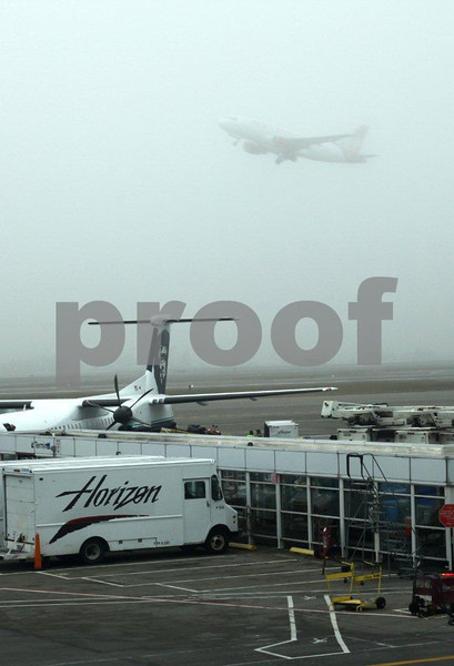 A plane takes off in heavy fog.