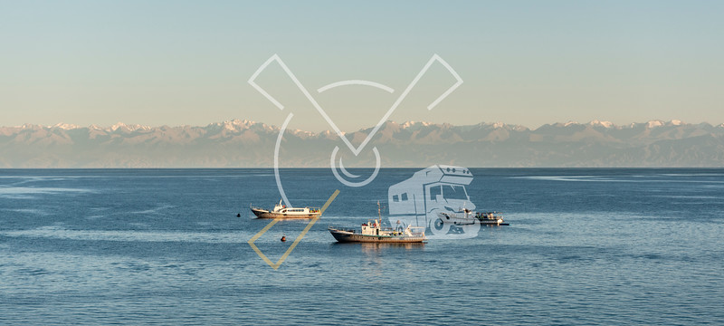 Tourist boats at Cholpon-Ata on the lake of Issyk-Kul in Kyrgyzstan with the Tian Shan mountains in the background