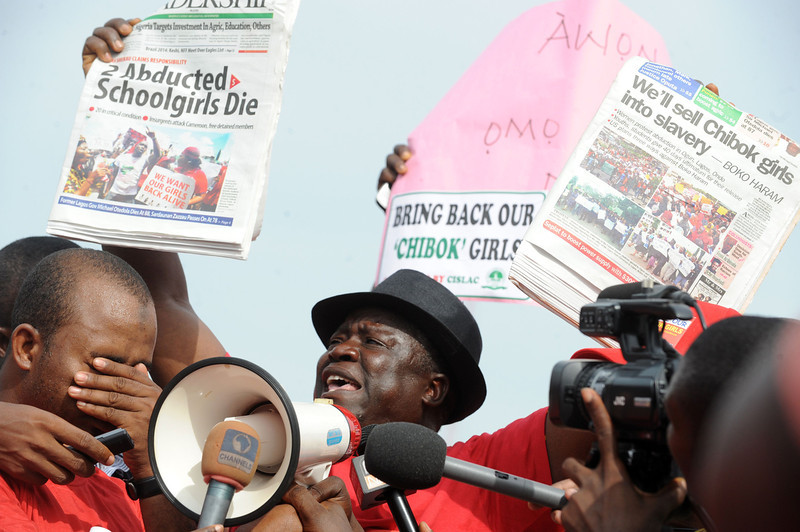 ". Leader of Chibok community in Abuja Hosea Sambido (R) raises a newspaper reporting the death of two of the abducted Chibok school girls during a rally pressing for the girls\' release in Abuja on May 6, 2014, ahead of World Economic Forum. Members of civil society groups marched through the streets of Abuja and to the Nigerian defence headquarters to meet with military chiefs, to press for the release of more than 200 Chibok school girls abducted three weeks ago. Suspected Boko Haram Islamists have kidnapped eight more girls from Nigeria\'s embattled northeast, residents said on May 6, after the extremist group\'s leader claimed responsibility for abducting more than 200 schoolgirls last month and said in a video he was holding them as ""slaves\"" and threatened to \""sell them in the market\"". (PIUS UTOMI EKPEI/AFP/Getty Images)"