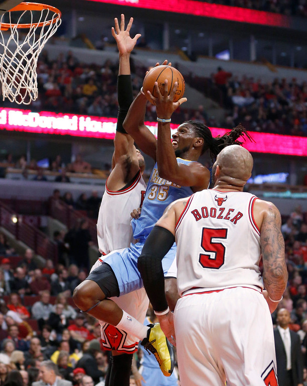. Denver Nuggets forward Kenneth Faried (35) goes to the basket between Chicago Bulls\' Carlos Boozer (5) and Taj Gibson during the first half of an NBA basketball game Friday, Feb. 21, 2014, in Chicago. (AP Photo/Charles Rex Arbogast)