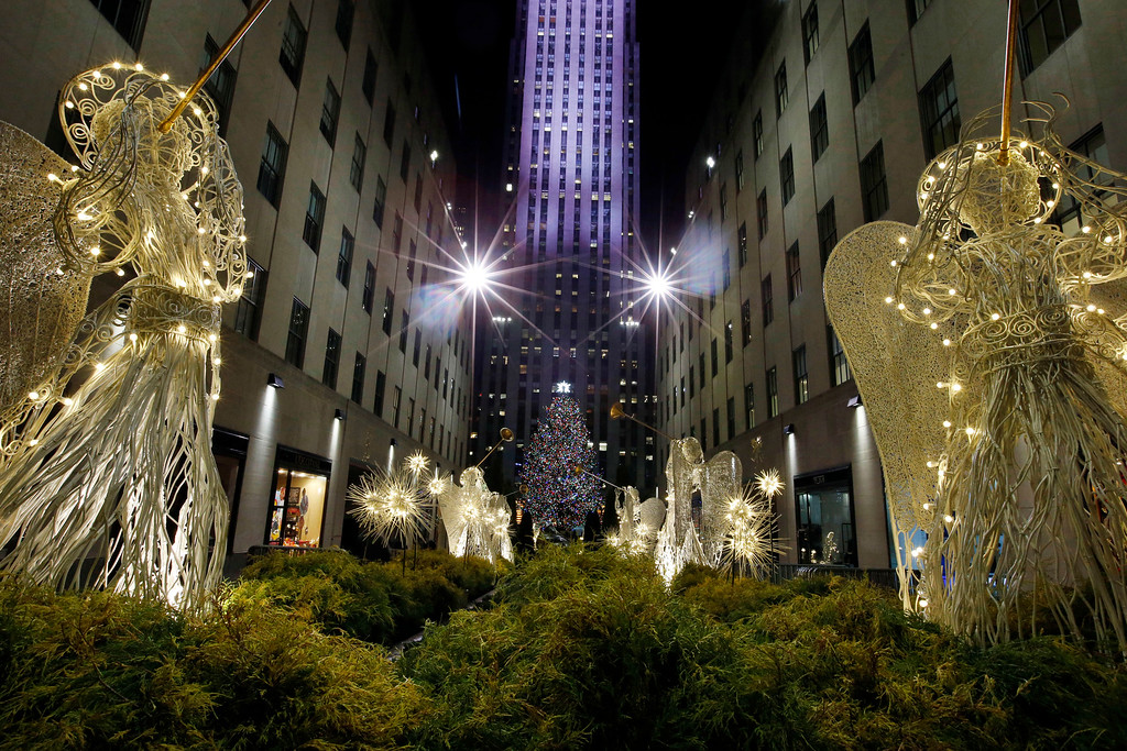 . The Rockefeller Center Christmas tree can be seen through the Channel Gardens following a lighting ceremony, Wednesday, Dec. 3, 2014, in New York.  Weighing in at approximately 13 tons, the 85-foot tall, 90-year-old Norway Spruce will be adorned with 45,000 energy efficient LED lights. (AP Photo/Jason DeCrow)