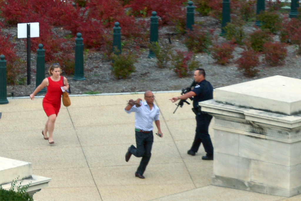 """. People run for cover as police converge to the site of a shooting October 3, 2013 on Capitol Hill in Washington, DC. The US Capitol was placed on security lockdown Thursday after shots were fired outside the complex, senators said. \""""Shots fired outside the Capitol. We are in temporary lock down,\"""" Senator Claire McCaskill said on Twitter. Police were seen running within the Capitol building and outside as vehicles swarmed to the scene. AFP PHOTO / Mandel NGAN/AFP/Getty Images"""