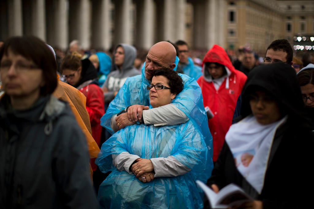 . People pray as Pope Francis leads a solemn ceremony in St. Peter\'s Square at the Vatican Sunday, April 27, 2014. Pope Francis has declared his two predecessors John XXIII and John Paul II saints in an unprecedented canonization ceremony made even more historic by the presence of retired Pope Benedict XVI. (AP Photo/Emilio Morenatti)