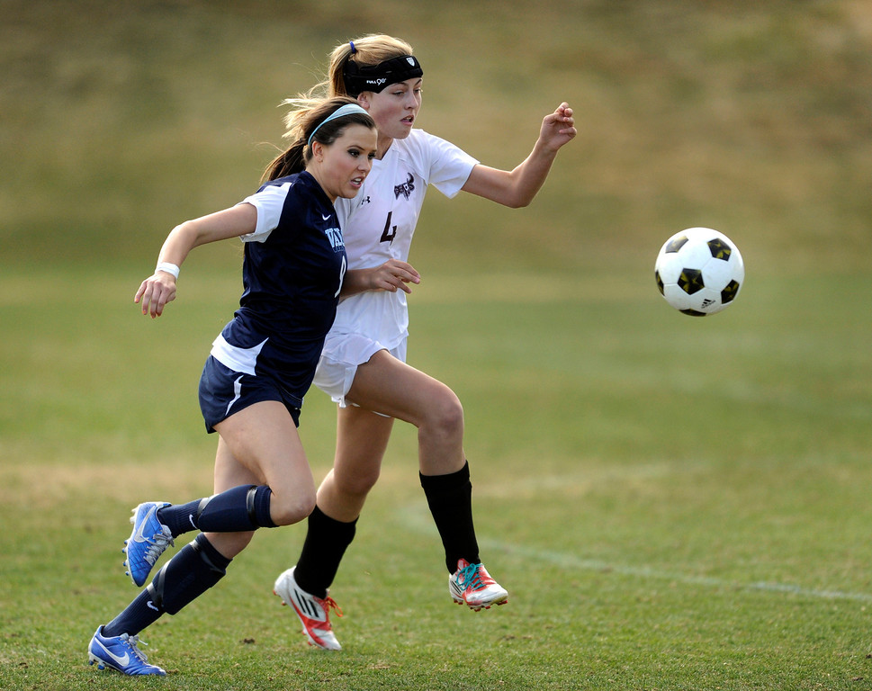 . PARKER, CO. - APRIL 2: Valor senior forward Hannah Hommel (9) tried to get past Demons defender Riley Sanders (4) in the first half. The Valor Christian High School girl\'s soccer team defeated Golden 4-1 Wednesday night, April 3, 2013.  Photo By Karl Gehring/The Denver Post)