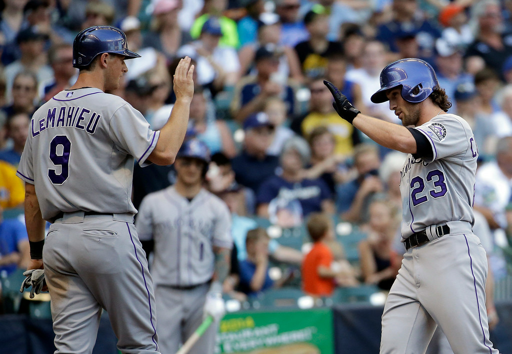 . Colorado Rockies\' Charlie Culberson (23) is congratulated by Vinny Castilla (9) after hitting a two-run home run during the eighth inning of a baseball game against the Milwaukee Brewers Sunday, June 29, 2014, in Milwaukee. (AP Photo/Morry Gash)