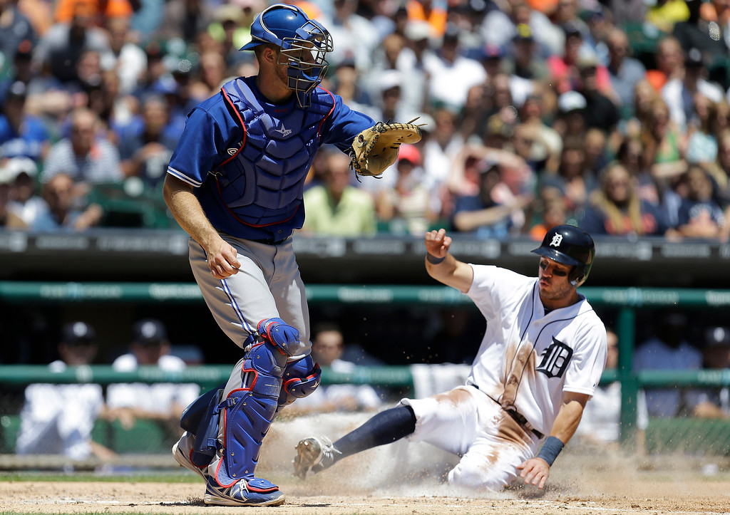 . Detroit Tigers\' Ian Kinsler scores on a Torii Hunter sacrifice fly as Toronto Blue Jays catcher Erik Kratz waits for the throw in the third inning of a baseball game in Detroit, Thursday, June 5, 2014. (AP Photo/Paul Sancya)